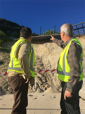 Photo 1-L-R_Group Operations Mgr Steve Bennett and CEO Steve Edmonds survey the erosion underneath the viewing platform of the park's guest lounge.jpg