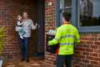 Coles Online team member Tom greeting customer Bec and her daughter Autumn at their front door (Small).jpg